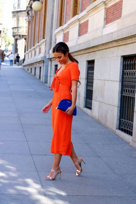 Vestido naranja con sandalias doradas